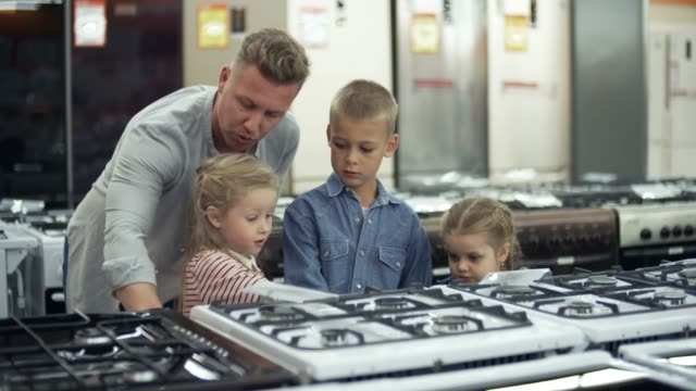 Cute Children Watching Kitchen Stove with Dad in Home Appliance Store Playful little boy and two girls discussing kitchen oven with smiling father while shopping together in home appliance store appliance stock videos & royalty-free footage