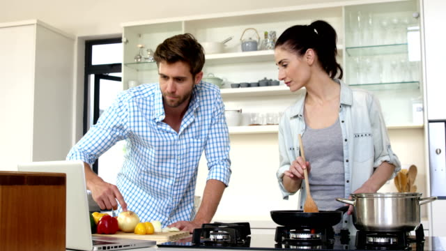 vídeos de stock e filmes b-roll de cute couple learning how to cook by watching a tutorial - cooker happy