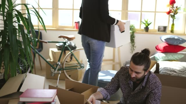 Cute couple sitting in new home around unpacked boxes
