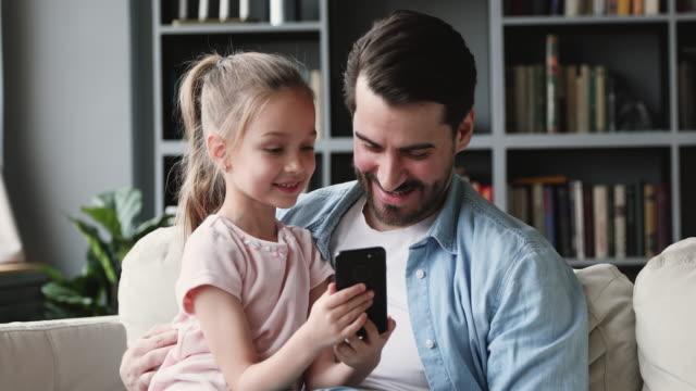 かわいい娘の未就学児はお父さん面白いビデオを示すスマートフォンを保持します - 娘点の映像素材/bロール