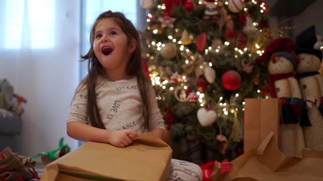 クリスマスツリーの下でプレゼントに驚いたかわいい有頂天の子供 ビデオ