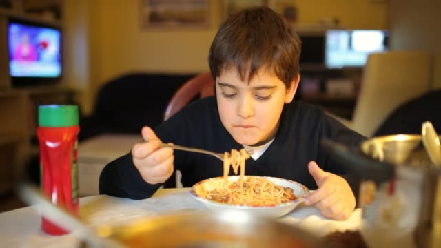 Cute elementary age boy eating spaghetti for dinner in dinning room