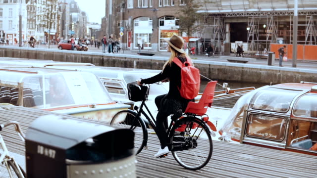 Cute European girl rides bicycle along river quay. Touristwoman in hat on a city bike in Amsterdam. Real time side view Cute European girl rides bicycle along river quay. Touristwoman in hat on a city bike in Amsterdam. Real time side view. Happy travel blogger. Amsterdam, Netherlands. Daily commuter. Creative manager. amsterdam stock videos & royalty-free footage