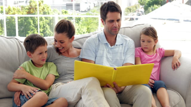 Cute family relaxing together looking at photo album video