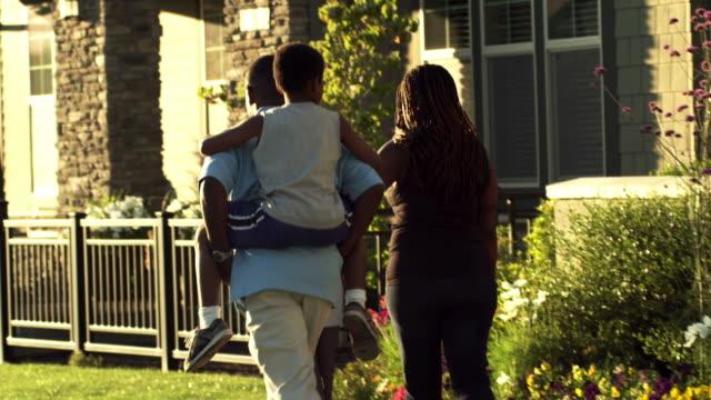 vídeos de stock, filmes e b-roll de linda família caminhada - calçada