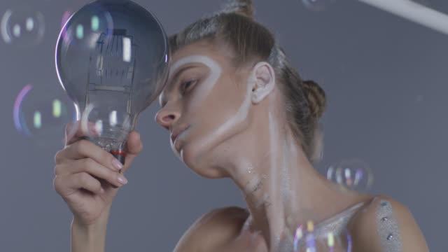 cute fashion model in stage make-up behind bubbles, holding light bulb. fashion video. - гримировальные краски стоковые видео и кадры b-roll