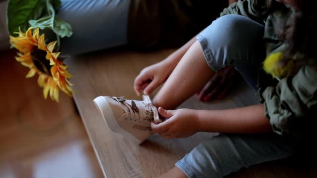 carino ragazza alla moda legare le scarpe - annodare video stock e b–roll