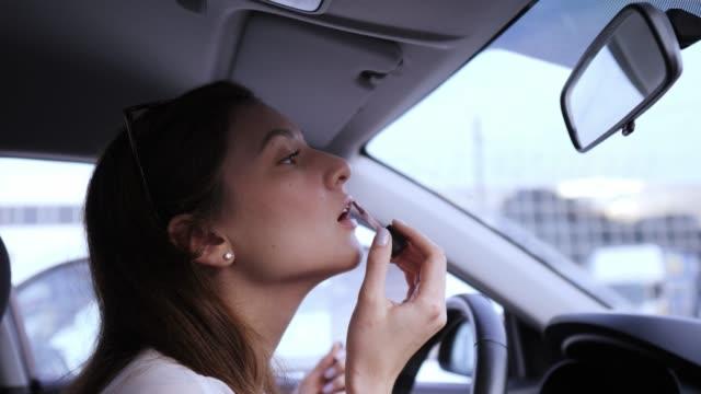 Cute female driver applies lipstick to the car. Makeup before work. Lip balm Cute female driver applies lipstick to the car. Makeup before work. Lip balm lip balm stock videos & royalty-free footage
