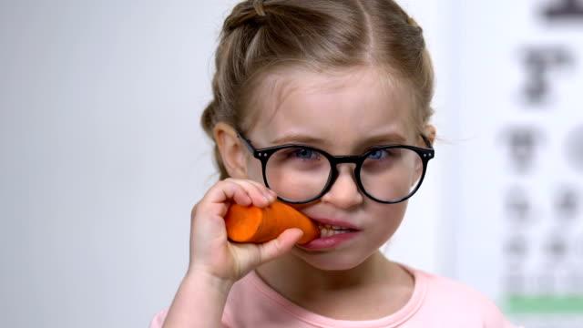 Cute female eyeglasses biting carrot, food improving vision, beta-carotene Cute female eyeglasses biting carrot, food improving vision, beta-carotene carrot stock videos & royalty-free footage