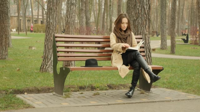 cute female starts to read a book and turning pages while sitting on a bench in autumn park wearing trench and brown scarf alone. - садовая скамья стоковые видео и кадры b-roll
