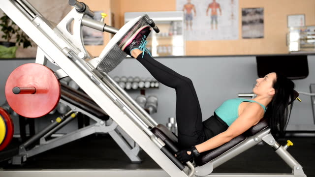 stockvideo's en b-roll-footage met schattig fit meisje doet oefeningen op de simulator - bankdruktoestel