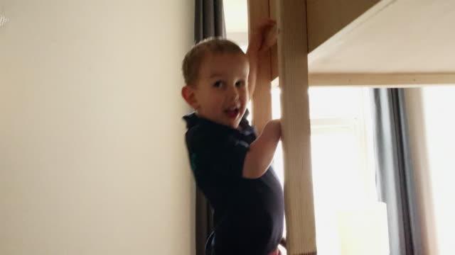 stockvideo's en b-roll-footage met een leuke, vijf jaar oude kaukasische jongen loopt in zijn kamer, klimt de houten ladder van zijn stapelbed, en legt op zijn kussen in zijn slaapkamer - ladder