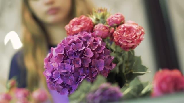 vídeos de stock e filmes b-roll de cute florist picking flowers in a bouquet. florist preparing flower bouquet. - trabalho de design