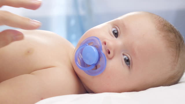 cute four month-old baby in blanket. close up. - ciuccio video stock e b–roll