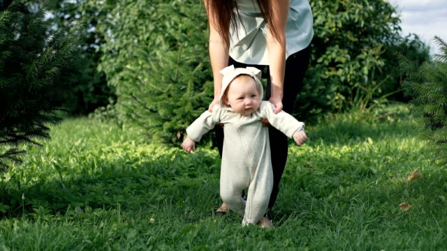 Cute funny happy baby making first steps on a green lawn in a sunny summer garden. video