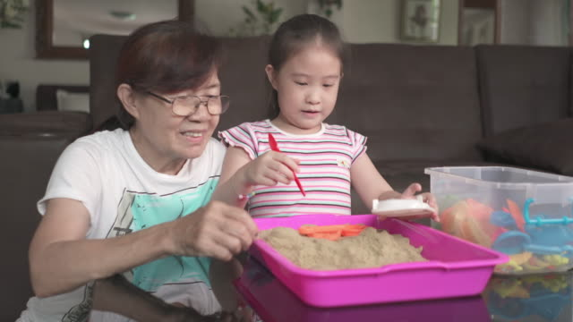 Cute genius girl crafting sand with grandmother in living room at home