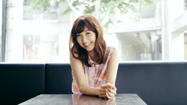 かわいい思いやりの若いアジアの女の子を、カフェ - ストリートファッション点の映像素材/bロール