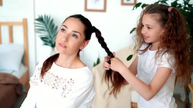 Cute girl braids her mom hair in braid, focus on daughter, slow motion
