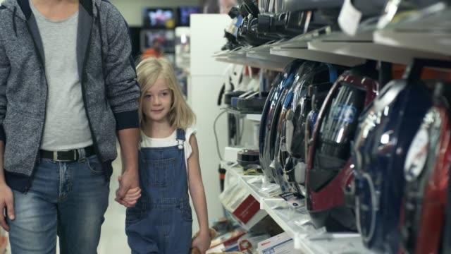 Cute Girl Choosing Vacuum Cleaner with Dad