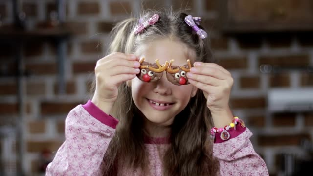 Cute girl covering eyes with homemade cookies video