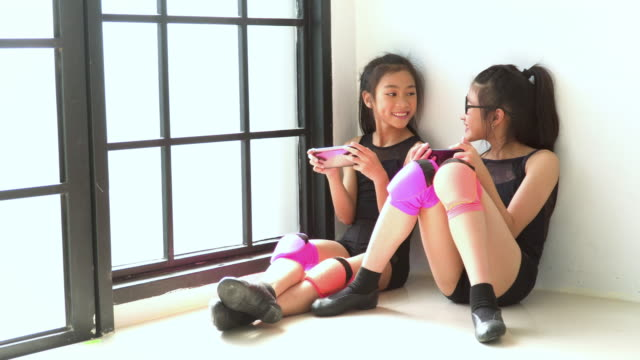 cute girl dancer and partner taking a break by playing a smartphone - 8 9 anni video stock e b–roll