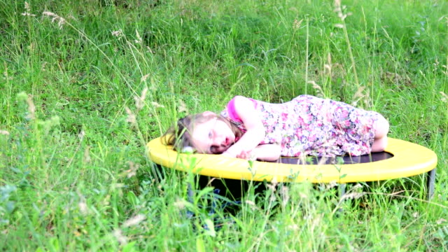 A cute girl dances in the natural garden. Little girl dances and jumps on a small trampoline. Little girl wears floral dress video