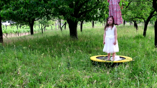A cute girl dances in the natural garden. Little girl dances and jumps on a small trampoline. Little girl wears white wedding dress video