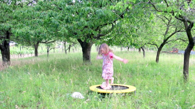 A cute girl dances in the natural garden. Little girl dances and jumps on a small trampoline. Little girl wears floral dress and white hat video