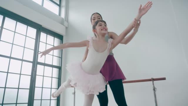 Cute girl doing ballet for her hobby beside lovely teacher