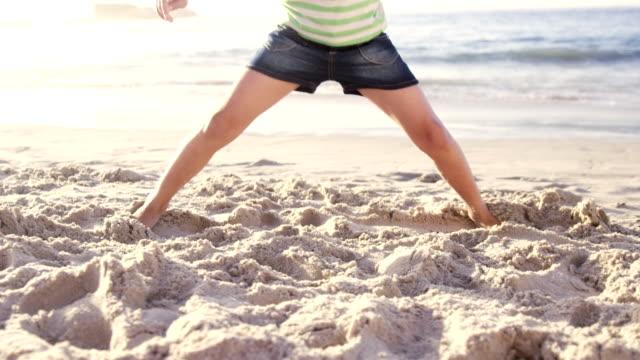 Cute girl doing split on the beach Cute girl doing split on the beach in slow motion doing the splits stock videos & royalty-free footage