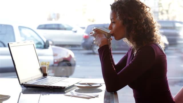 симпатичный девочка, пить кофе в кафе в городе - служащая стоковые видео и кадры b-roll