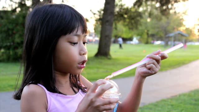 Cute Girl Drinks Her Cool Slush Drink A cute little eight year old Asian girl enjoys a nice cool slushy drink on a hot summer day at the park. Need more clips of kids? straw stock videos & royalty-free footage