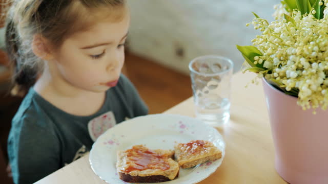 cute girl eating breakfast at the table with a bouquet of flowers video