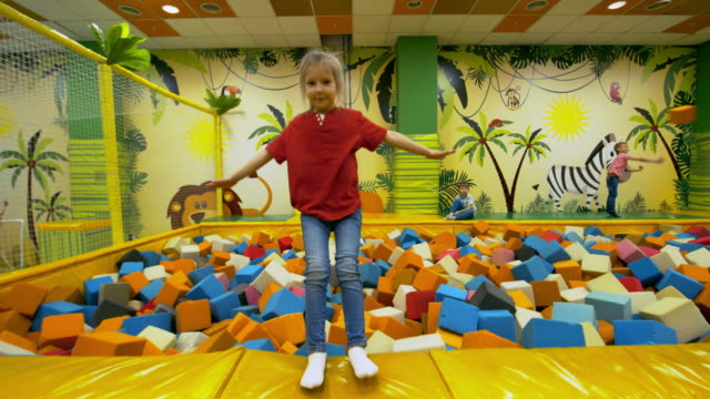 Cute Girl Falling in Cube Pit Dolly shot of adorable little girl of elementary school age falling backwards into cube pit and lying in multicolored foam cubes when spending time in indoor playground playroom stock videos & royalty-free footage
