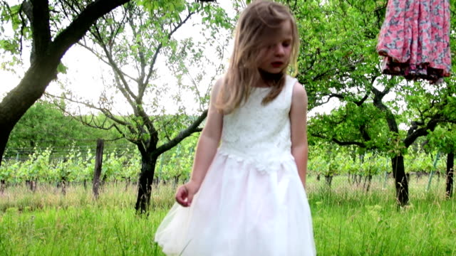 A cute girl has a rest in the nature garden. Little girl wears white wedding dress video