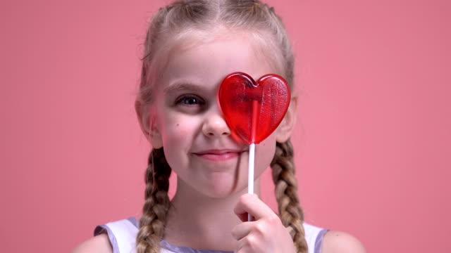可愛的女孩有樂趣, 閉上眼睛與心形棒棒糖, 情人節 - 波板糖 個影片檔及 b 捲影像