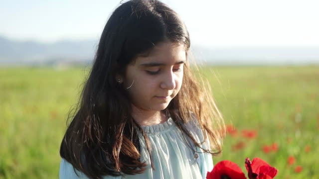 Cute girl in a flowery field of red poppies