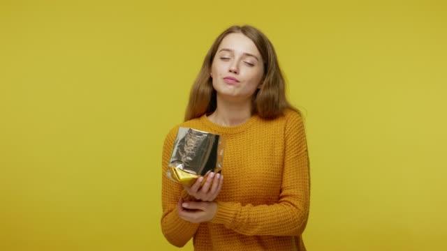 cute girl in casual sweater eating crisp chips with expression of pleasure, enjoying tasty fried food - węglowodan jedzenie filmów i materiałów b-roll