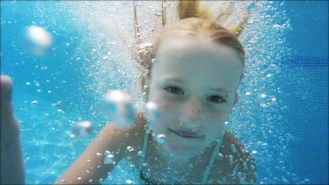 Cute girl in jumping into pool -slowmotion video