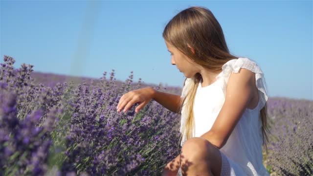 cute girl in lavender flowers field - wschodnio europejski filmów i materiałów b-roll