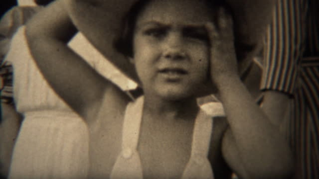 1937: cute girl in leather cowboy hat wipes sweat from face bends hat. - cowgirl video stock e b–roll