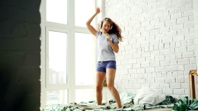 パジャマでかわいい女の子は無線ヘッドホン好きな曲を聴いて、ヘアブラシが自宅のベッドの上で踊って歌います。現代のライフ スタイル、人々 と楽しいコンセプト。 - ブラシ点の映像素材/bロール