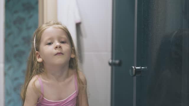 cute girl in pink shirt gargles sore throat at large mirror