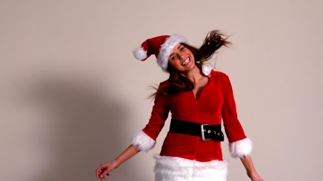かわいい女の子をジャンプと笑顔のサンタのコスチューム - サンタの帽子点の映像素材/bロール