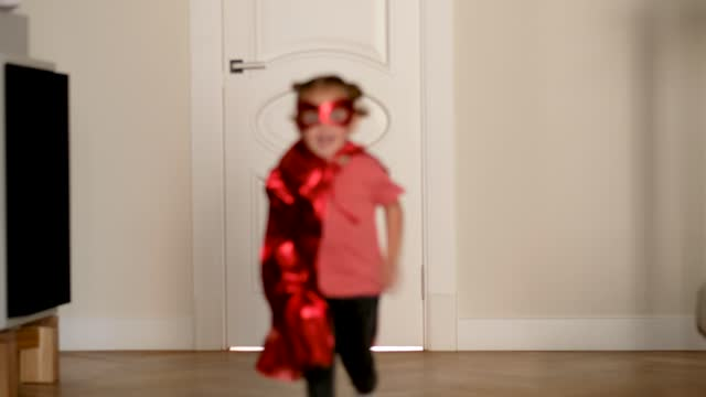 vídeos de stock e filmes b-roll de cute girl in shiny red cape and mask runs to camera in room - baby super hero