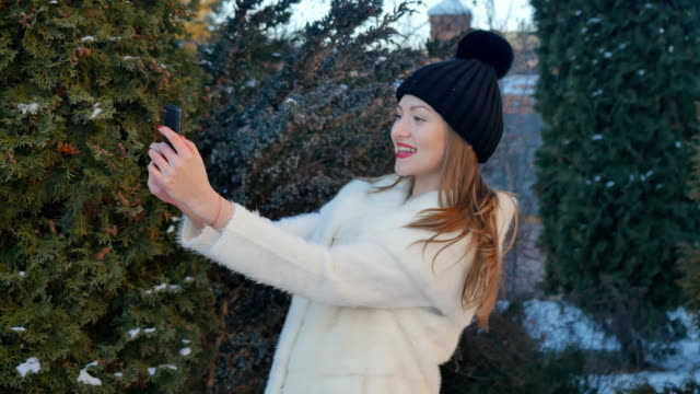 Cute girl in white fur coat makes a selfie at fir-tree background Cute girl with red lips, in black hat and dressed on fur coat is using a smartphone outdoors. Stylish young woman is making a selfie a her phone at fir-tree background. Pretty female photographs herself near the fir-trees. red lipstick stock videos & royalty-free footage