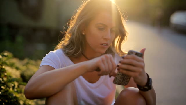 cute girl looking at her phone - generazione y video stock e b–roll