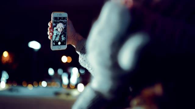niedliche mädchen macht selfie im winter. konzentrieren sie sich auf das telefon. im hochformat. - girlande dekoration stock-videos und b-roll-filmmaterial