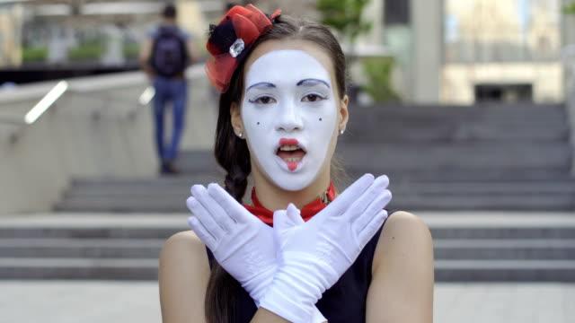 cute girl mime playing with hands on camera - гримировальные краски стоковые видео и кадры b-roll