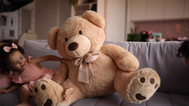 Cute girl playing with a big teddy bear